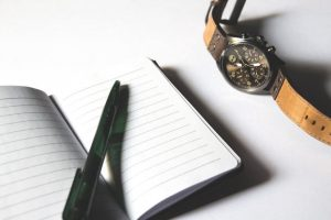An image of a notebook and a watch