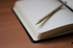 An empty notebook with a wooden pencil on top of it.