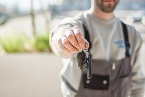 A uniformed man holding car keys