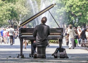 Man playing a piano, people are walking in the background, Manhattan