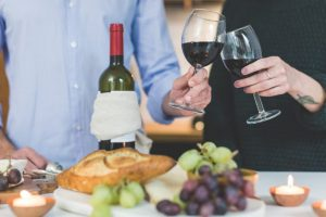 Bread, grapes and hands holding glasses with red whine.