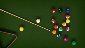 A pool table with cue and balls