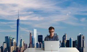 Man sitting in front of a computer, Manhattan skyline behind him.