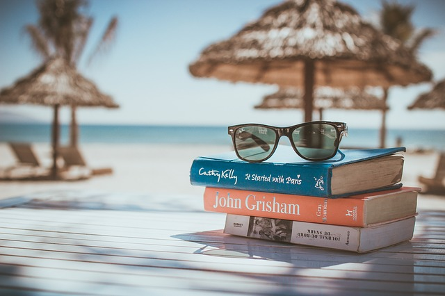 A pair of women's sunglasses on a pile of books, with a beach in the background.