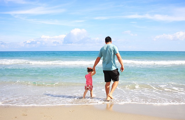 A father and a child walking along the beach.