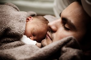 A man sleeping with his baby.