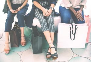 Women with shopping bags sitting on a bench.