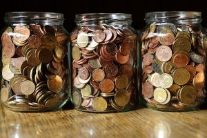 Three jars full of coins you will be able to save if you opt for moving into a smaller apartment.
