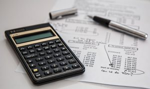There is a piece of paper with some figures, a pen and a calculator you need to make plans when moving your business.