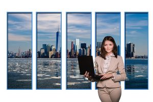 A woman with a laptop in front of five-pieced picture of NYC.