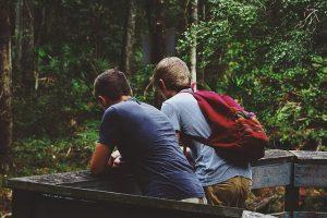 Two friends talking in woods.