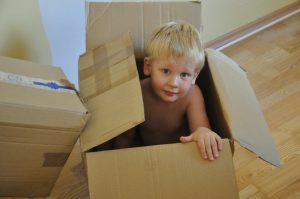 A kid in a moving box trying to prepare for an international move.