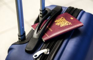 A passport and a suitcase you need to prepare for an international move.