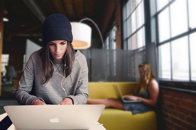 Woman on the laptop thinking about the pros and cons of renting a coworking space.