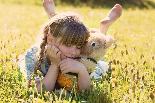 A girl with a teddy bear.