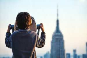 The boy looks through binoculars at the city