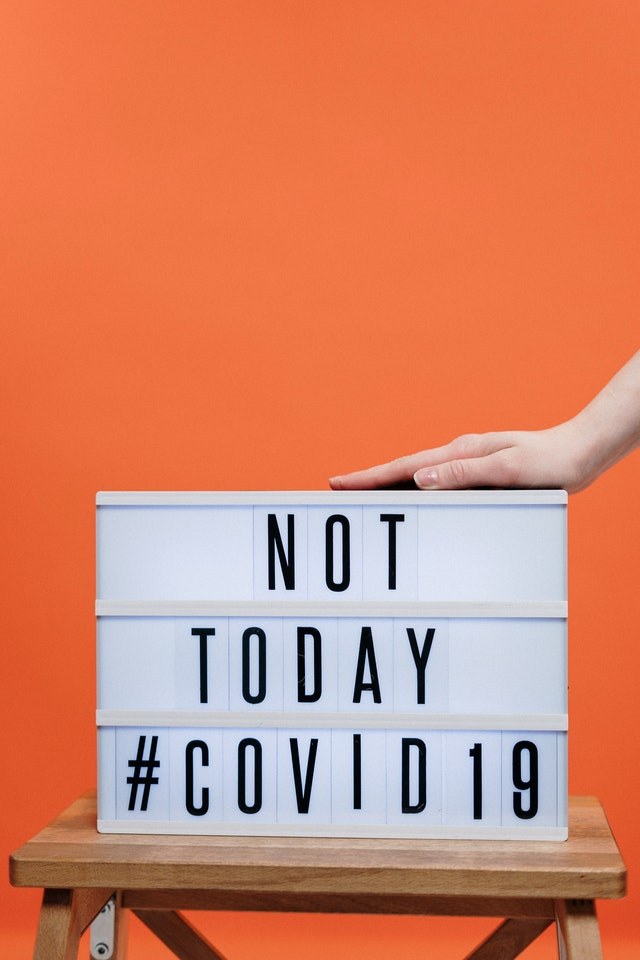 "A sign that says ""NOT TODAY COVID-19"" that signifies how you need to be responsible when preparing your business for relocation to another state in 2020."