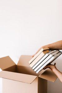 A person puting some books in a cardboard box