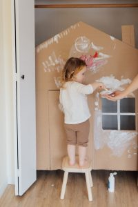 Girl playing with a cardboard castle