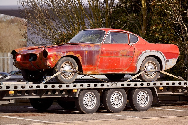 An old car on a flatbed trailer