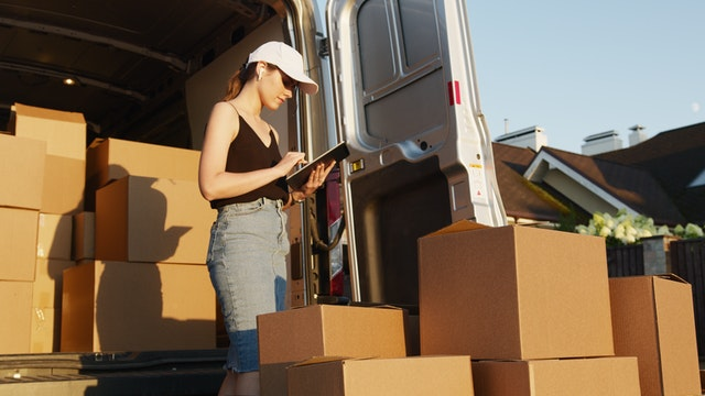 A woman inventorying box weight as one of the factors that affect moving company quotes.