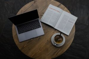 a book and a laptop on wooden table