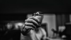 a black and white photo of a man holding a one dollar bill