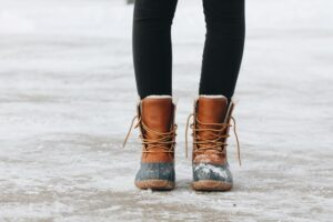A girl in her boots on the snow as once you move from NYC to Miami you won't use your winter boots!